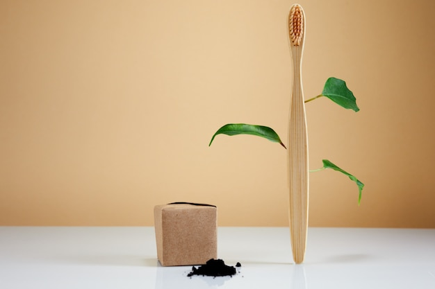 Spazzolino da denti in legno di bambù con foglie e dentifricio al carbone nero come concetto creativo ecologico. prodotto di bellezza bagno biologico naturale.