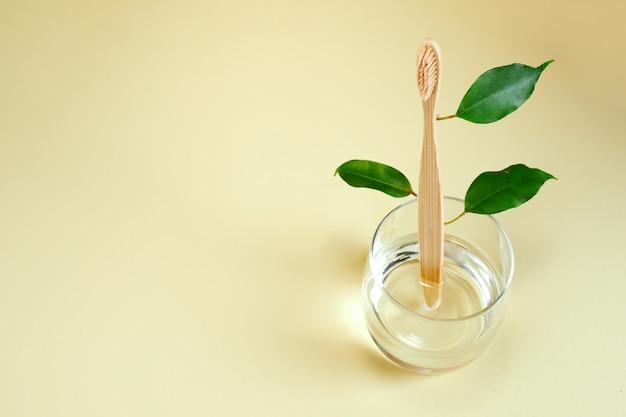 Spazzolino da denti in legno di bambù con foglie su vetro. zero rifiuti, concetto ecologico. la vita senza plastica