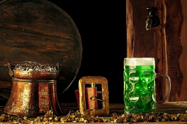 Lo sfondo della botte di legno con un sacco di monete d'oro e un grande boccale di birra con un fiocco verde. sfondo per la celebrazione del giorno di san patrizio e il concetto di festa religiosa