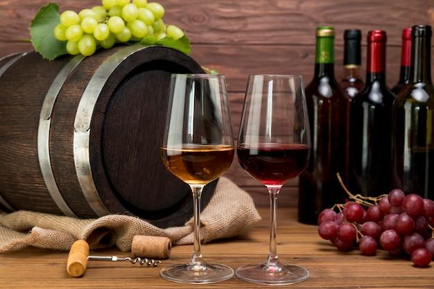 Botte di legno con bottiglie e bicchieri di vino