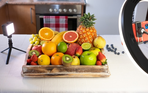 Cesto di legno pieno di frutta fresca su sfondo bianco. agrumi, papaia, ananas, fragole, melograno, mirtillo. luci e dispositivi elettronici per lo streaming