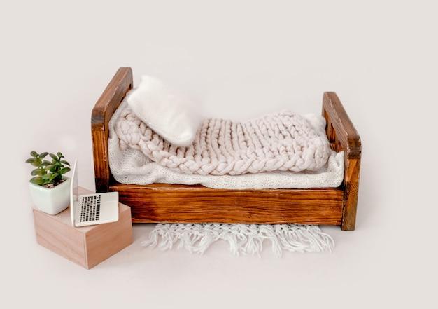 Arredamento letto in legno per servizio fotografico in studio neonato con coperta a maglia e primo piano del cuscino. mobili fotografici per neonati e laptop giocattolo