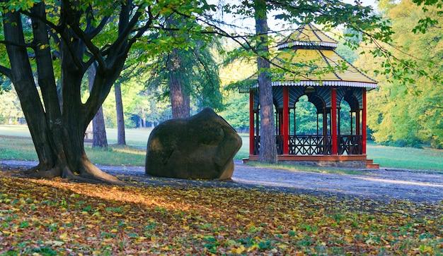 Belvedere in legno, grande pietra e percorso pedonale nel parco cittadino d'autunno