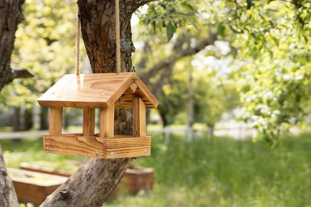 Mangiatoia per uccelli in legno, una casa per uccelli su un albero in estate