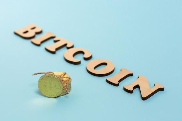 Lettere di bitcoin in legno e bitcoin dorati sulla superficie blu
