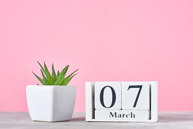 Calendario a blocchi di legno con data 7 marzo e pianta su sfondo rosa