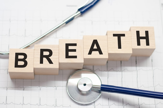 Blocco di legno forma la parola respiro con stetoscopio sul desktop del medico. concetto medico. concettuale di assistenza sanitaria per ospedali, cliniche e attività mediche.