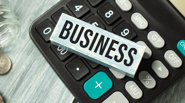 Blocco di legno con business sulla calcolatrice, concetto di affari.