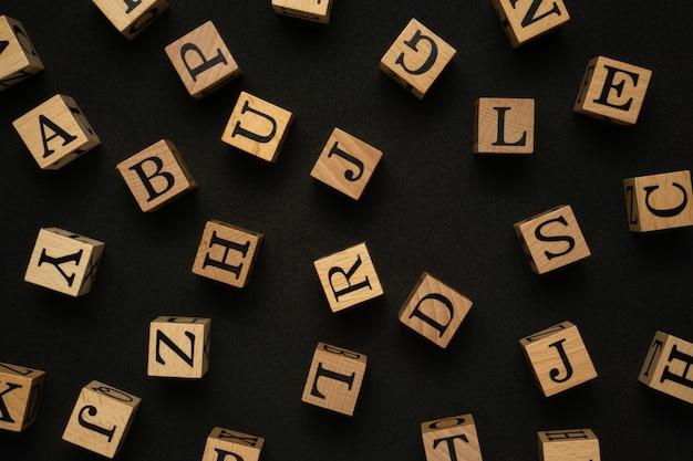 Blocco di legno con lettere maiuscole su sfondo nero.