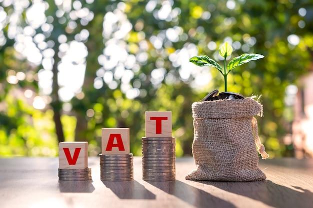 Blocco di legno con testo iva su monete impilate e albero su concetto di iva tong iva addebitata dal governo sull'acquisto di beni o servizi.