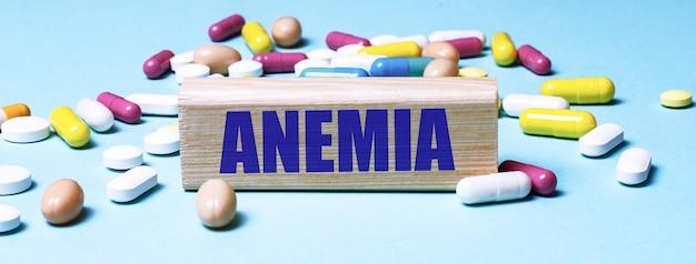 Un blocco di legno con la parola anemia si trova su uno sfondo blu tra pillole multicolori