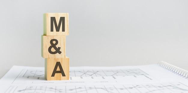 Blocco di legno con le parole m e a - acronimo - acquisizioni di fusioni. i blocchi di legno m e a sono sullo sfondo grigio della carta. concetto di affari. spazio per il testo a destra. vista frontale.