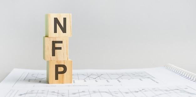 Ceppo di legno con parole pfn - acronimo - utile operativo netto. i blocchi di legno nfp sono sullo sfondo grigio della carta. concetto di affari. spazio per il testo a destra. vista frontale.