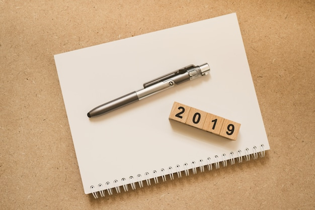 Blocco di legno anno 2019 e penna sul taccuino bianco