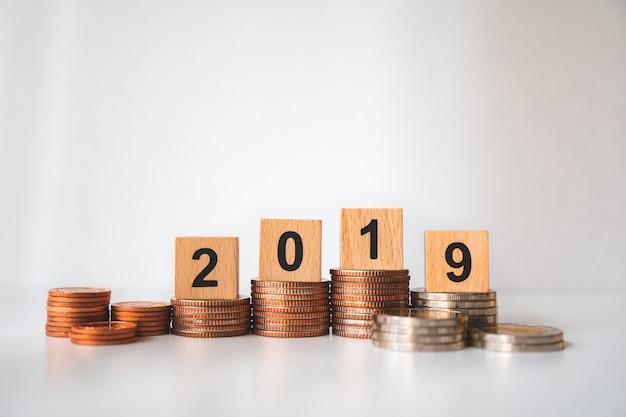 L'anno 2019 del blocco di legno sulle monete della pila facendo uso come concetto di affari e finanziario