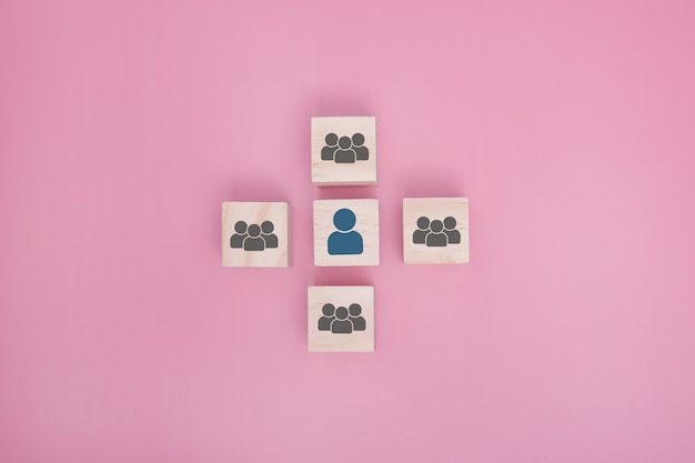 Blocchi di legno collegati tra loro su sfondo rosa. cooperazione, lavoro di squadra, rete e concetto di comunità.
