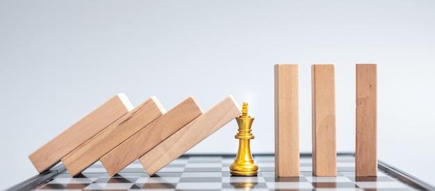 Blocchi di legno o domino che cadono alla figura dorata del re degli scacchi. business, risk management, soluzione, regressione economica, assicurazioni