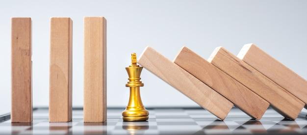 Blocchi di legno o domino che cadono sulla figura dorata del re degli scacchi