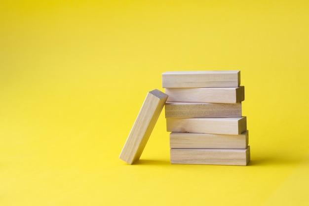 Blocchi di legno piegati nella torre su sfondo giallo. successo, crescita, vittoria, vittoria, sviluppo
