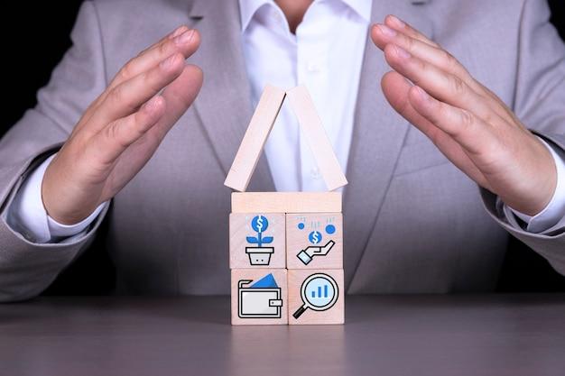 Blocchi di legno a forma di casa con icone che simboleggiano crescita, profitto, interesse, deposito bancario, deposito.