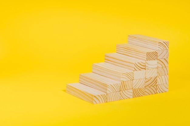 Blocchi di legno che formano scala su sfondo giallo yellow