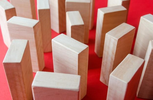Blocchi di legno su uno sfondo rosso concetto di un labirinto di armadi o di una densa costruzione urbana