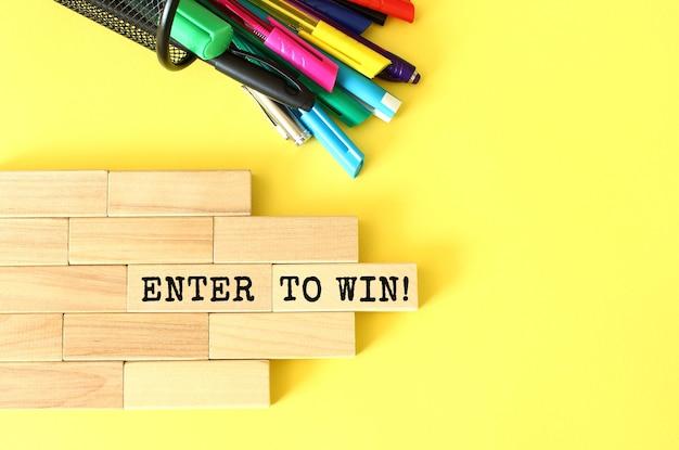 Blocchi di legno impilati accanto a penne e matite su sfondo giallo. entra per vincere testo su un blocco di legno. concetto di affari