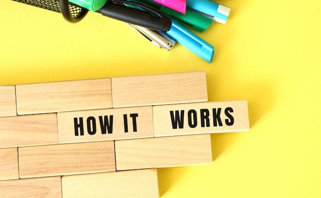 Blocchi di legno impilati accanto a penne e matite su sfondo giallo. come funziona testo su blocco di legno. concetto di affari