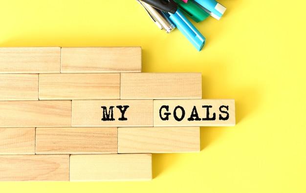 Blocchi di legno impilati accanto a penne e matite su sfondo giallo. i miei obiettivi testo su un blocco di legno. concetto di affari