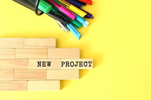 Blocchi di legno impilati accanto a penne e matite su sfondo giallo. nuovo progetto testo su blocco di legno. concetto di affari