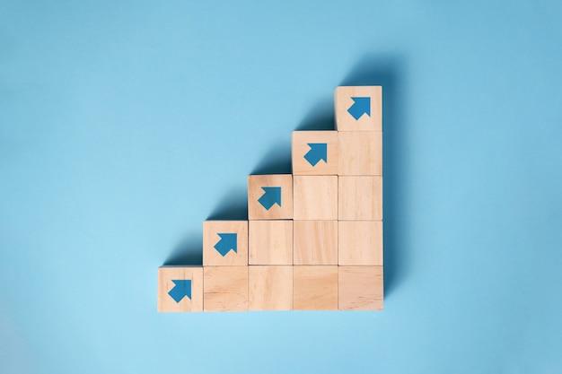 Scala di blocchi di legno con icona a forma di freccia, concetto di pianificazione aziendale.
