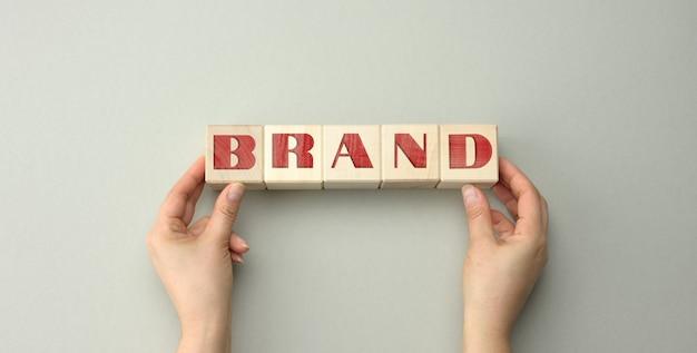 Blocchi di legno con la scritta del marchio e due mani femminili. concetto di fiducia del marchio per prodotti, azienda, design del logo e strategia aziendale