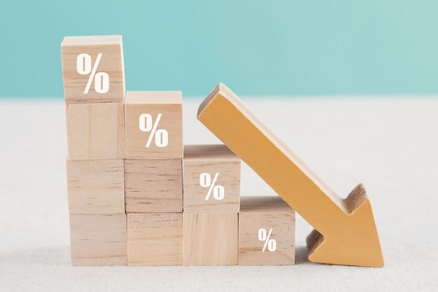 Blocchi di legno con segno di percentuale e freccia in basso, crisi di recessione finanziaria, calo dei tassi di interesse, concetto di riduzione degli investimenti
