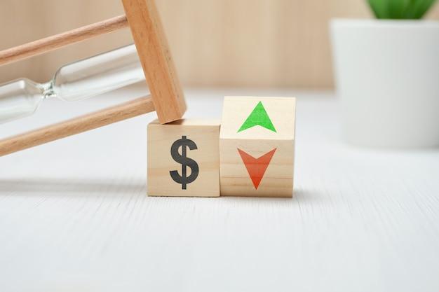 Blocchi di legno con il simbolo del dollaro americano e le frecce su e giù.