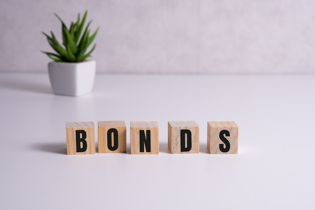Blocchi di legno con la parola obbligazioni. un'obbligazione è un titolo che indica che l'investitore ha fornito un prestito all'emittente. prestito equivalente. obbligazioni non garantite e garantite.