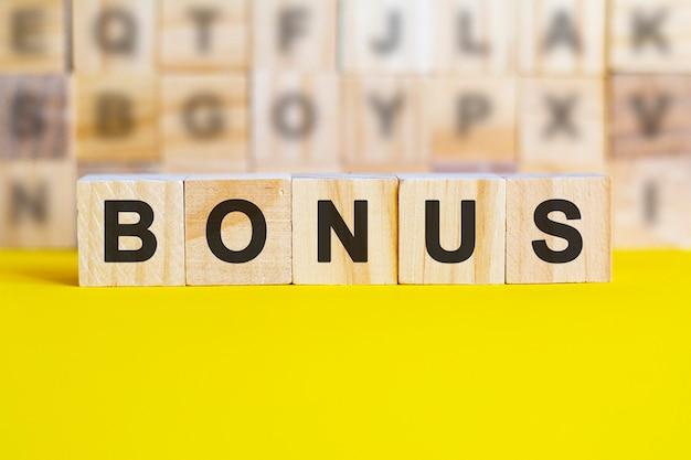 Blocchi di legno con la parola bonus. un'obbligazione è un titolo che indica che l'investitore ha concesso un prestito all'emittente. prestito equivalente. obbligazioni non garantite e garantite. affari e finanza