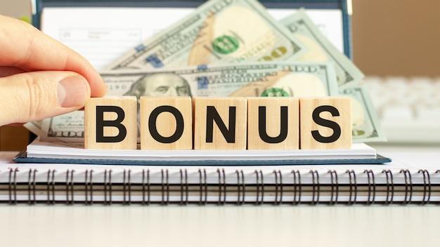 Blocchi di legno con la parola bonus. concetto di affari su cubi di legno e sfondo di dollari