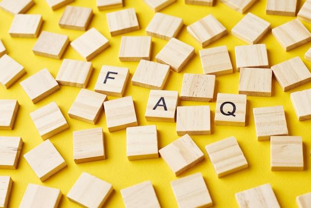 Blocchi di legno con la parola faq su baclground giallo. concetto di domande frequenti