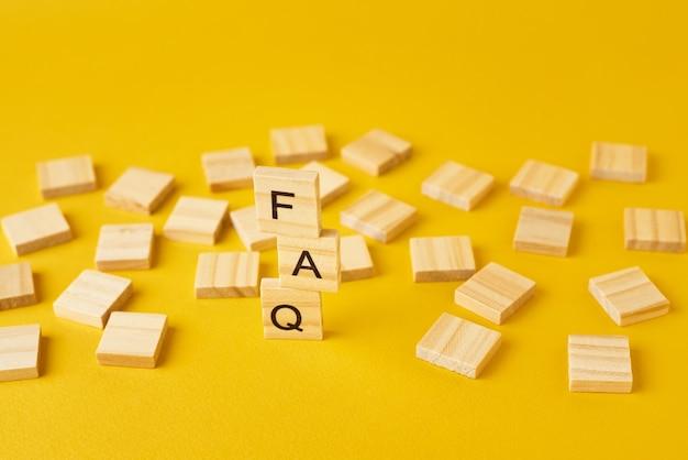 Blocchi di legno con la parola faq su baclground giallo. concetto di domanda frequente