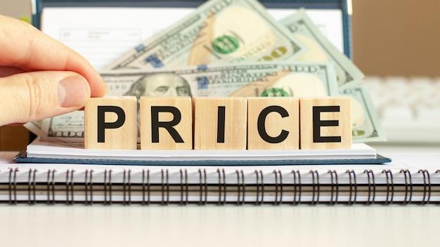 Blocchi di legno con la parola prezzo, concetto di affari su cubi di legno e sfondo di dollari