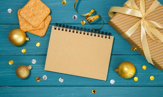 Superficie blu in legno con decorazioni natalizie dorate, quaderno, cracker e confezione regalo