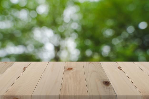 Bordo di legno sopra il fondo verde vago della natura, tavola di legno vuota di prospettiva sopra il backgroun di defocus