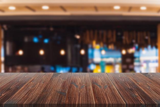 Tavola di legno sopra offuscata all'interno del fondo del ristorante