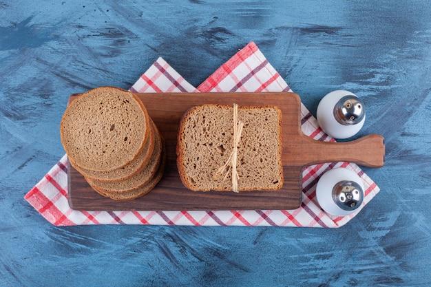 Una tavola di legno di pane nero e spezie su una tovaglia.