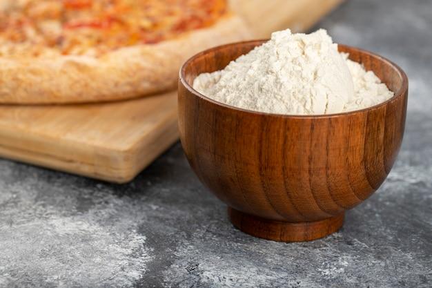 Tavola di legno di pizza di formaggio e ciotola di farina su fondo di pietra.