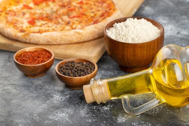 Tavola di legno di pizza di formaggio e condimenti vari su fondo di pietra.