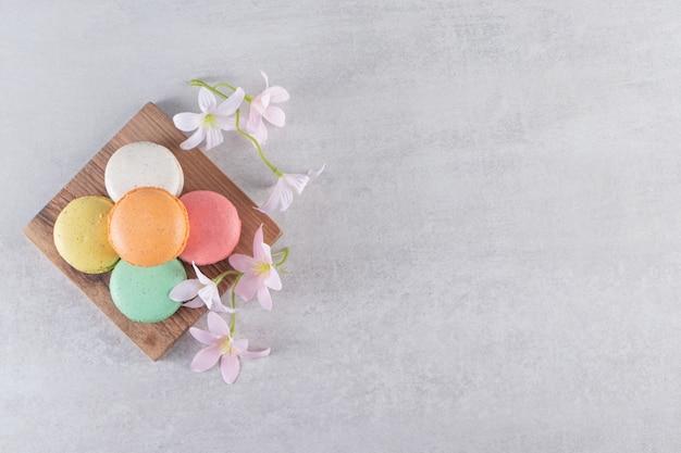 Tavola di legno di coloratissimi amaretti dolci con fiori sul tavolo di pietra.