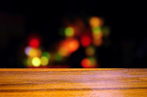 Tavola vuota in legno davanti alla luce colorata del bokeh nella notte