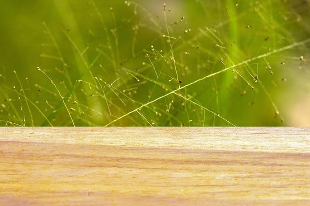 Tavola vuota del bordo di legno davanti ai fiori dell'erba su fondo verde per la visualizzazione del prodotto