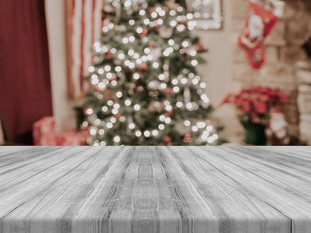 Piano d'appoggio vuoto del bordo di legno sul fondo vago dell'albero di natale.